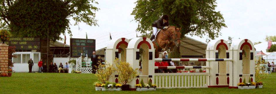 Tony and his horse jumping over a hurdle at an event.